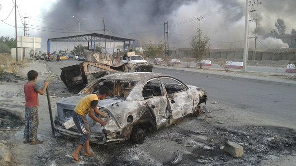 Criancas-observam-carro-destruido-apos-ofensiva-terrorista-em-Mosul-no-Iraque-size-598